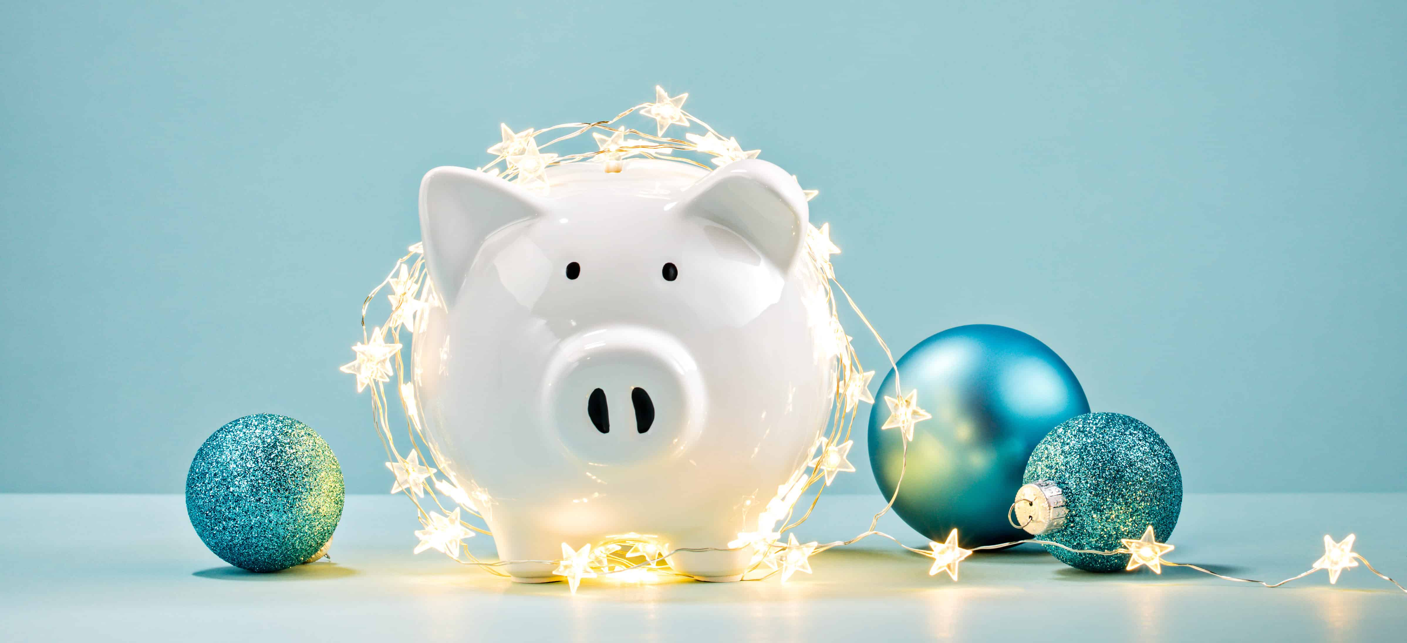 Piggy bank wrapped in a string of Christmas lights